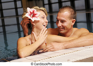 The pair in swimming pool - The young beautiful pair in...