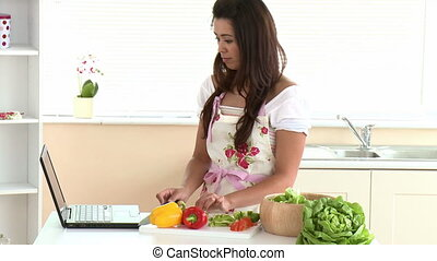 Happy woman using laptop while preparing dinner in the...