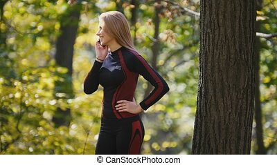 Young, sporty woman talking on cellphone at autumn park outdoor, close up