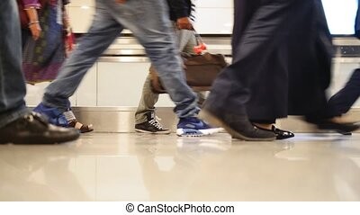 People walking with luggage in the international airport, close up shot of legs and shoes
