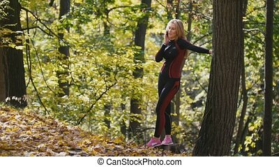 Young, sporty woman talking on cellphone at autumn park outdoor