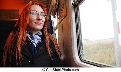 Attractive young woman with red hair and glasses looking out...