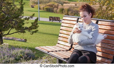young lady with Maine Coon cat seats on the bench