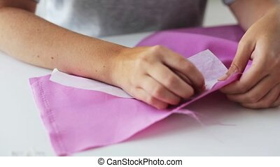 woman with pins stitching paper pattern to fabric - people,...