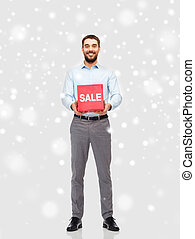 smiling man with red sale sign over snow - people, shopping,...