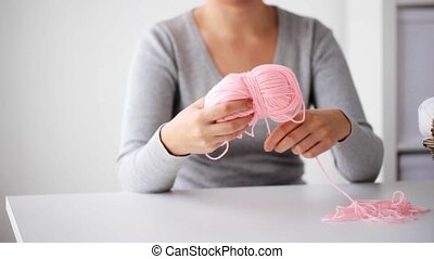 woman pulling yarn up into ball - knitting, people and...