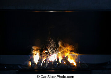 flame of firewood burning in modern fireplace - heating,...