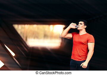 Athletic Man Drinking Water and Resting from Fitness Routine...