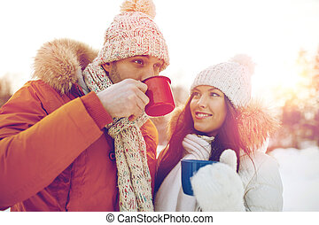 happy couple with tea cups over winter landscape - people,...