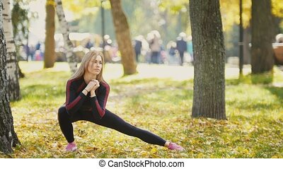 Sexy Attractive female blonde bikini-fitness model stretching in the autumn park on ground covered yellow leaves - legs flexibility