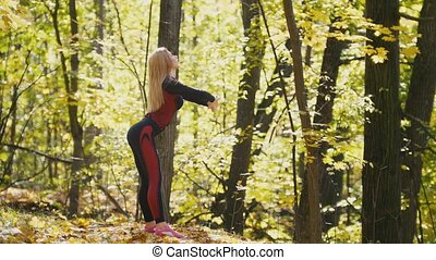 Girl having a training work-out in the autumn park. Sexy fitness-bikini blonde model in red suit and pink sneakers