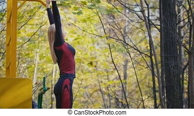 Young fitness female model Exercising in a Meadow at autumn park, Sports Outdoor Activities concept - exercises on the horizontal bar