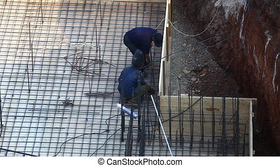 two man welding metal for concrete
