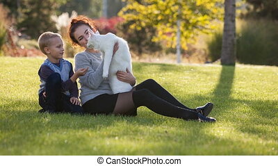 young lady and boy with Maine Coon cat on the grass