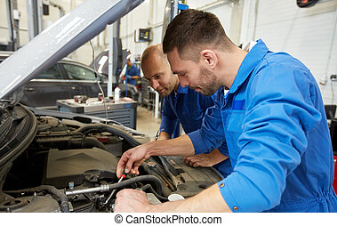 mechanic men with wrench repairing car at workshop - auto...