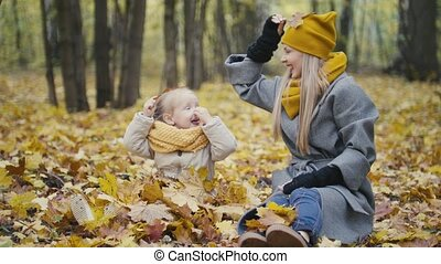 Mother and her daughter little girl walking in a autumn park...
