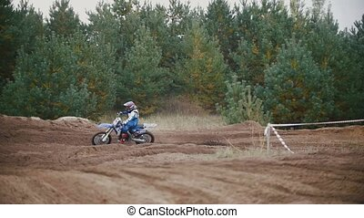 Motocross racer mxgirl on dirt bike jumping on track among...