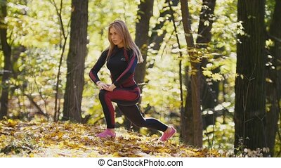 Woman doing fitness exercises outdoor. Female stretching in autumn forest. Slim girl at outdoor workout