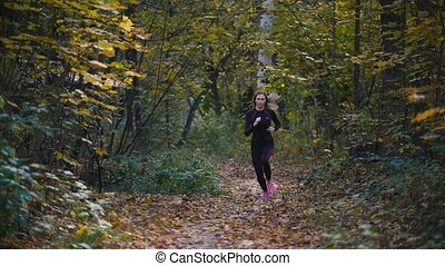 Young active female athlete exercising outdoor autumn park. Healthy women, slow-motion