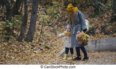 A cute little girl with blonde hair and her mom walking in...