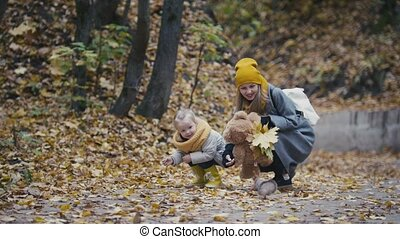 A cute little girl with blonde hair and her mom feed the red...