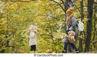 Mother and her daughter little girl walking in a autumn park - playing with Teddy Bear