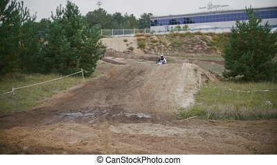 Motocross racer mxgirl on dirt bike jumping on track in...