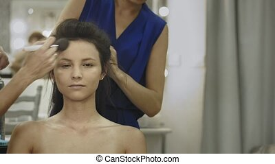 Professional make up artist working on a model - casual...