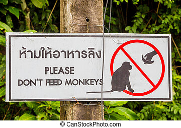 Do not feed monkeys sign in English and Thai