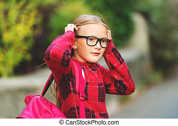 Outdoor portrait of a cute little 9 year old girl, wearing...