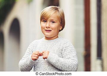 Outdoor portrait of cute 5-6 year old little boy, wearing...
