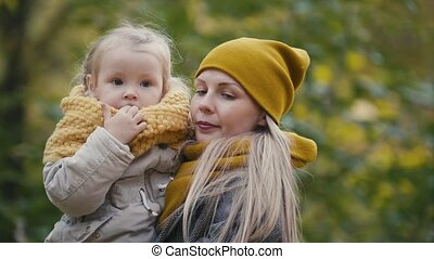 Mother and her daughter little girl playing in a autumn park...