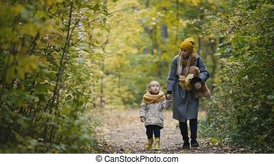 Mother and her daughter little girl walking in a autumn park - mommy, child and Teddy Bear