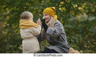Mother and her daughter little girl playing in a autumn park - mommy and child have fun and play Patty-cake