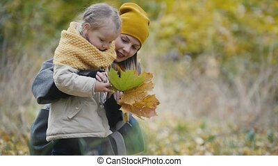 Mother and her daughter little girl playing in a autumn park - mom gives child collect leaves