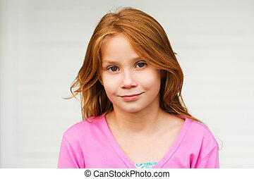 Outdoor portrait of cute little 8-9 year old girl with long red hair, wearing pink jacket, standing against white background