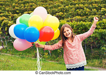 Happy little 8-9 year old girl with colorful balloons