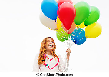 Happy little 8-9 year old girl with red hair holding...