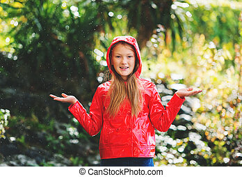 Adorable little 9 year old girl playing under the rain in...