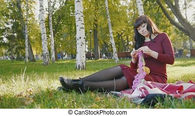 Beautiful pregnant woman in autumn park knitting needles,...