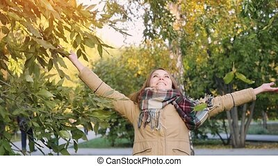Happy woman throws autumn leaves in the autumn park in...