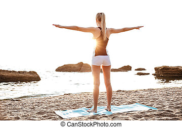 Back view of a beautiful young woman doing stretching...