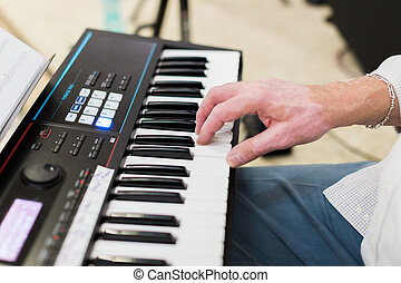 Keyboard player performing on stage live concert