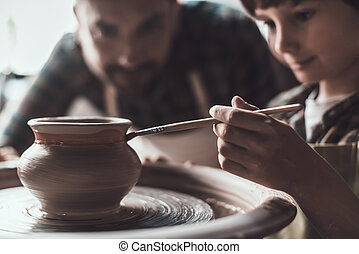 Pottery class. Little boy drawing on ceramic pot at the pottery class while man in apron standing close to him