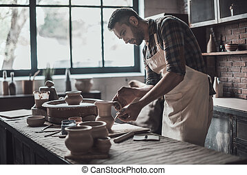Potter making jug. Confident young man in apron making ceramic jug at his workshop