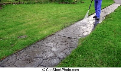 Long stone cobbled path and worker wash it. Garden...