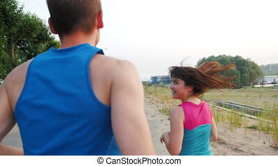Couple of young adult athletes: woman and man jogging on promenade . Healthy lifestyle concept, slow-motion