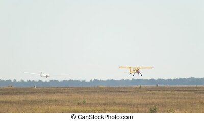 Plane take off and pulls glider on cable in air, telephoto