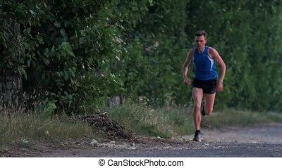 Sprinting runner man running at fast speed, jogging in park,...