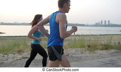 Couple of young adult athletes: woman and man running along promenade of river. Healthy lifestyle concept, slow-motion, rear view